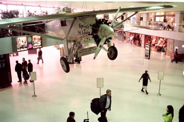 People walk near a replica of Charles Lindbergh's Spirit of St. Louis hanging from the ceiling at Lambert-St. Louis International Airport in this Jan, 15 1998, photo. UPI Bill Greenblatt