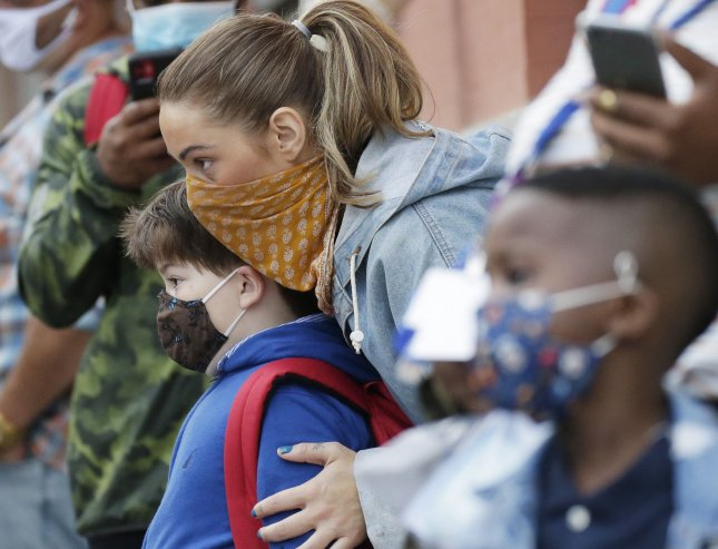 A child wears a face mask while being held by an adult as they wait on line to enter a school in New York City in September 2020, when the city opened schools with a combination of in-person learning and home schooling. File Photo by John Angelillo/UPI