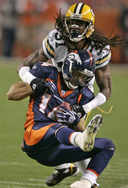 Green Bay Packers cornerback Al Harris (top) brings down Denver Broncos WR Brandon Stokley after a first down on a 18-yard second quarter pass reception at Invesco Field at Mile High in Denver on October 29, 2007. (UPI Photo/Gary C. Caskey)