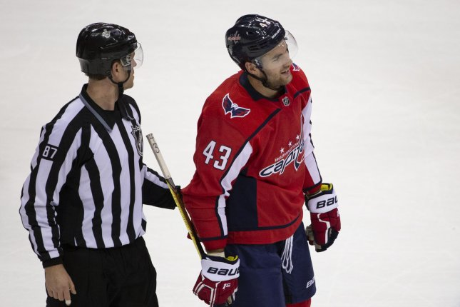 NHL Linesmen Devin Berg escorts Capitals right wing Tom Wilson (43) to the penalty box. Photo by Alex Edelman/UPI