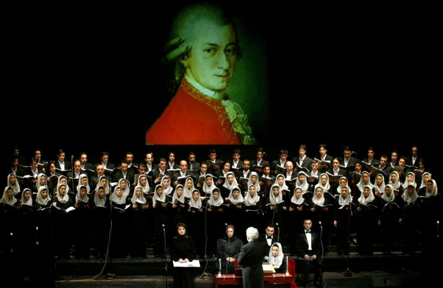Iranian-Armenian conductor Loris Tjeknavorian (bottom) leads the symphony orchestra in Vahdat (Unity) amphitheater as Mohammad Noori's group sings in front of an image of Mozart in Tehran, Iran on December 4, 2005. This concert was performed for the 250th anniversary of Mozart's death. (UPI Photo/Mohammad Kheirkhah)