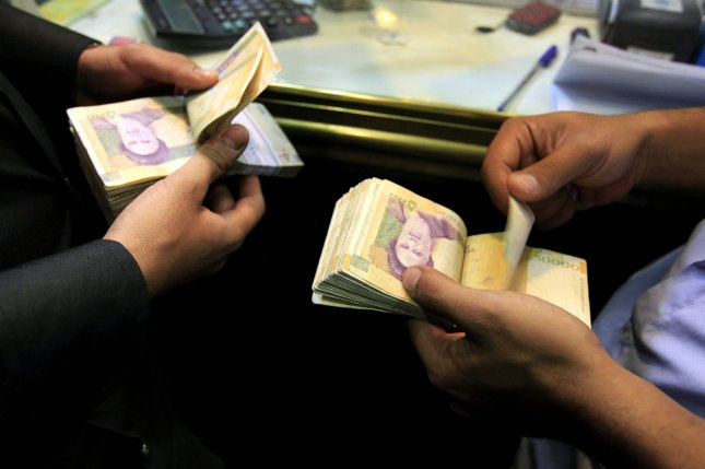 Iranian men count 50,000-rial banknotes bearing a portrait of Iran's late Leader Ayatollah Khomeini. Iran's currency has fallen to record lows against the U.S. dollar, prompting new currency policies. File Photo by Maryam Rahmanian/UPI
