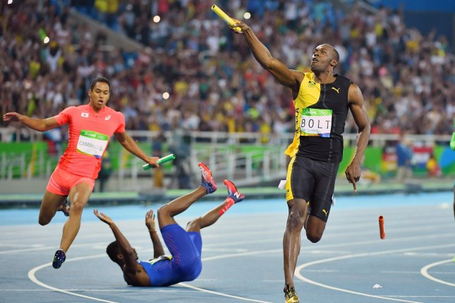 Trayvon Bromell of the United States tumbles to the track and looses his baton while Usain Bolt of Jamaica celebrates as he crosses the finish line after winning the gold medal in the Men's 4 x 100m relay final at Olympic Stadium at the 2016 Rio Summer Olympics in Rio de Janeiro, Brazil, on August 19, 2016. Bolt completes the olympic Triple-Triple with Jamaica's win in the 4x100m. Photo by Kevin Dietsch/UPI
