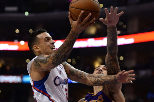 Los Angeles Clippers' Matt Barnes shoots over Los Angeles Lakers' Robert Sacre during second half action on January 10, 2014. File photo by Jon SooHoo/UPI