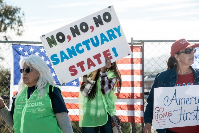 Demonstrators hold signs at an America First rally at the San Ysidro Port of Entry in California on December 15, 2018. On Wednesday, a federal appeals court said the Trump administration can withhold federal funds from states and cities with so-called sanctuary policies. File Photo by Ariana Drehsler/UPI