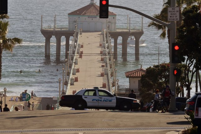 An unoccupied police car blocks the entrance to the pier in Manhattan Beach, Calif., on Monday, as the coronavirus pandemic disrupted the usual activities for Memorial Day weekend.  Photo by Jim Ruymen/UPI