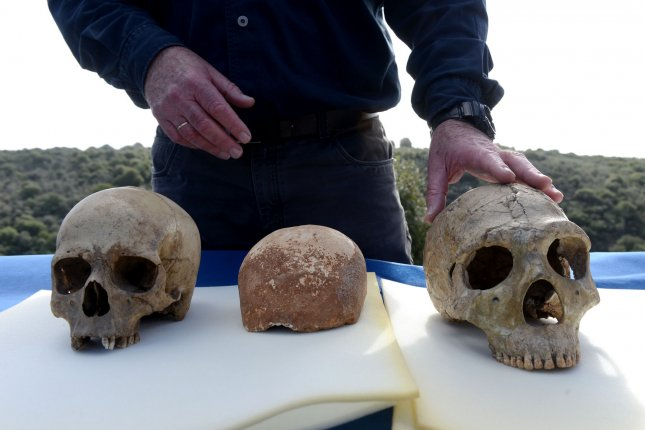 Professor Israel Hershkovitz of Tel Aviv University stands by a Homo sapien skull, left, a recently discovered 55,000-year-old human skull and a Neanderthal skull, right, at a press event outside the Manot Cave in the Western Galilee, Israel, on Jan. 28. A team of researchers from Tel Aviv University, Ben-Gurion University and the Israel Antiquities Authority say the 55,000-year-old skull is one of the most important discoveries in the study of human evolution. The rare skull constitutes the earliest fossilized evidence outside of Africa indicating that today's human population originated in Africa. The partial ancient skull offers clues to the first modern Europeans, as researchers suggest the population from which the skull is derived had recently migrated out of Africa and established itself in the Levantine before moving to Europe. Photo by Debbie Hill/UPI