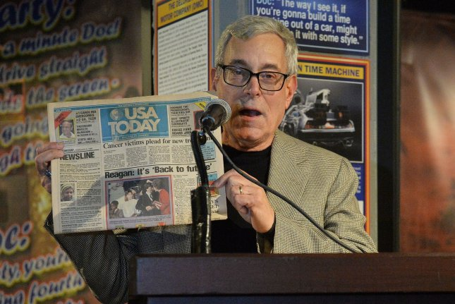 Creator, producer and writer Bob Gale holds up a 1986 issue of USA Today with the headline Reagan: Back to the Future during a private gala to celebrate the opening of 'Back To The Future' Trilogy: The Exhibit. Photo by Jim Ruymen/UPI
