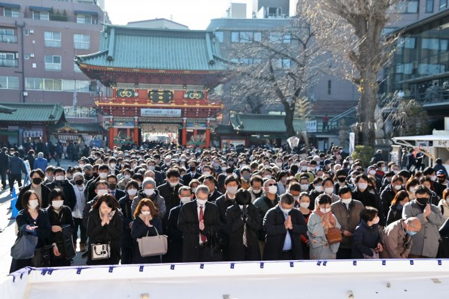 Office workers, wearing face masks to ward off the coronavirus but without social distancing, pray at Kanda Myojin shrine on the first business day of the new year in Tokyo on Monday. Photo by Keizo Mori/UPI