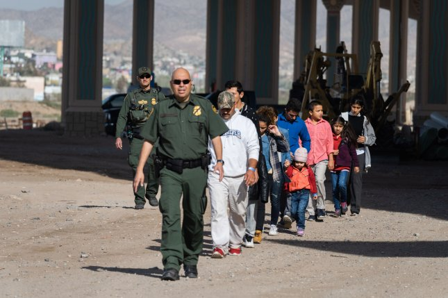 Migrants walk to the Border Patrol processing center after crossing the Rio Grande River into the United States in El Paso, Texas, on March 27, 2019. File Photo by Justin Hamel/UPI