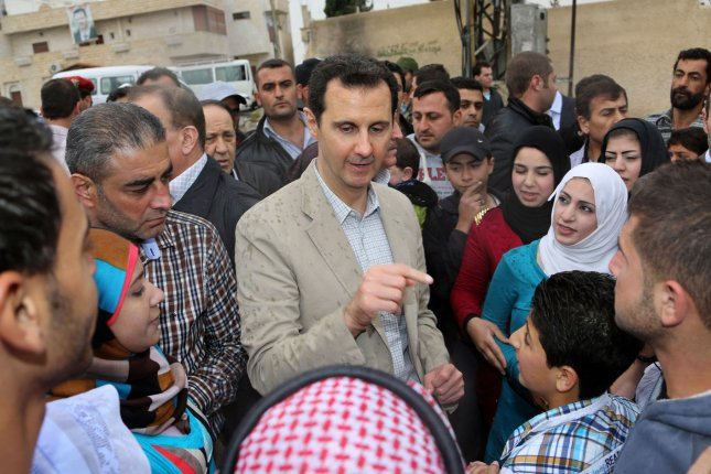 In this photo released by Syria's national news agency, Syrian President Bashar al-Assad talks with people during his visit to Ein al-Tinah village, northeast of Damascus, in Syria on April 20, 2014. (UPI)