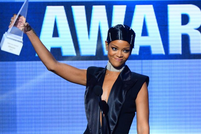 Rihanna accepts the AMA's first icon award from her mother Monica Braithwaite at the 41st annual American Music Awards held at Nokia Theatre L.A. Live in Los Angeles on November 24, 2013. UPI/Jim Ruymen
