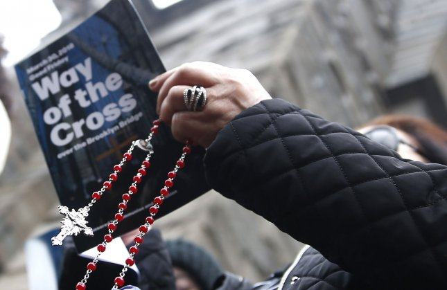 A woman holds a Crucifix as the choir sings at the Way of the Cross event on March 30 in New York City. A Gallup study found that Catholic church attendance in the United States has been on a steady decline in the last decade. Photo by John Angelillo/UPI