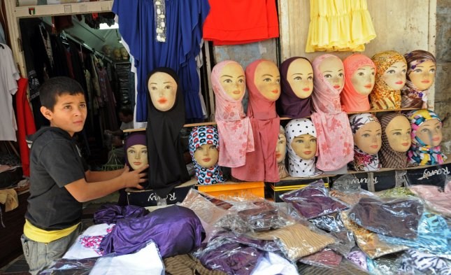 A Palestinian boy arranges a headscarf display in a shop in the Old City of Jerusalem during the holy month of Ramadan, August 30, 2009. In Austria on Wednesday, lawmakers announced plans to ban the headscarf in public schools for girls under 10. File Photo by Debbie Hill/UPI