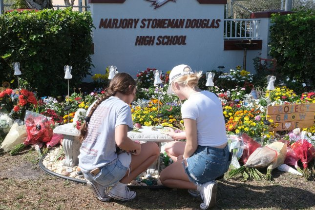 Students lay down notes and flowers at a makeshift memorial in front of Marjory Stoneman Douglas High School in Parkland, Fla., on February 14 -- one year after the mass shooting there. File Photo by Gary Rothstein/UPI