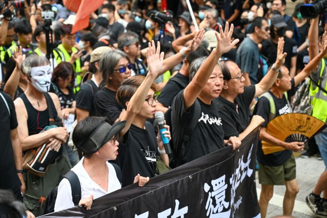 Former politician Lee Cheuk-yan and other politicians and activists hold up five fingers to signify the five demands of their protest movement in Hong Kong on October 1, 2019. Photo by Thomas Maresca/UPI