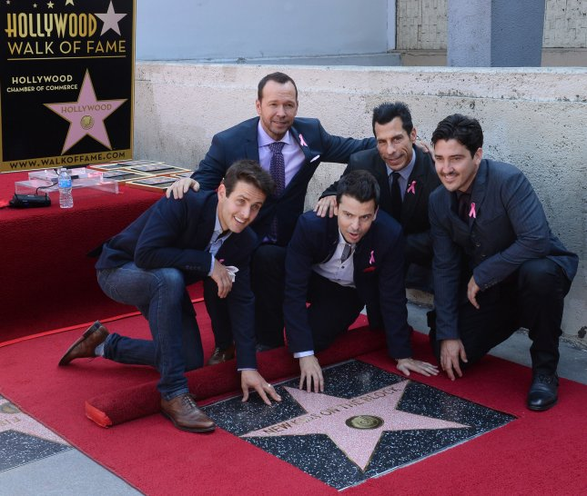 New Kids On The Block band members Joey McIntyre, Donnie Wahlberg, Jordan Knight, Danny Wood and Jonathan Knight (L-R) gather around their star after the American boy band was honored with the 2,530th star on the Hollywood Walk of Fame during an unveiling ceremony in Los Angeles on October 9, 2014. UPI/Jim Ruymen