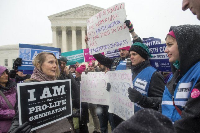 An anti-abortion supporter argues with supporters of women's rights groups as they participate in a rally in front of the Supreme Court in Washington, D.C. on March 25, 2014. A new study found complications from abortion are rare. File photo by Kevin Dietsch.