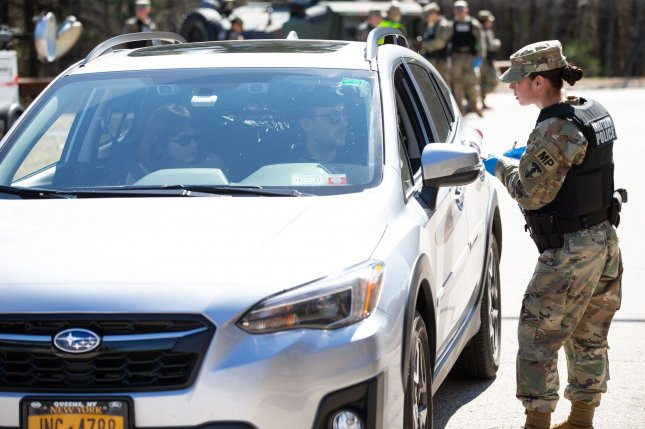 A member of the Rhode Island Army National Guard takes down information from people in a vehicle with New York license plates at a rest area in Richmond on Friday. Photo by Matthew Healey/UPI