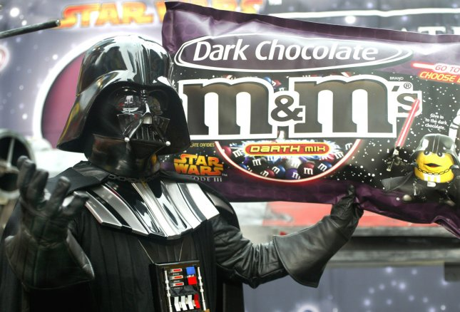 Star Wars character Darth Vader holds up a model of the new Star War-themed M&M's which is unveiled in Time Square on March 29, 2005 in New York City. Masterfoods USA, the makers of M&M's, is marketing a dark chocolate version of the popular candy as they promote the movie Star Wars:Episode III Revenge of the Sith. (UPI Photo/Monika Graff)