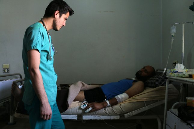 A Syrian medic helps a wounded man in the hospital after airstrikes hit Syria's Aleppo province on May 21, 2016. A report to the U.N. Security Council found that both the Syrian government and the Islamic State militant group have used chemical weapons on civilians. File Photo by Ameer Alhalbi/UPI