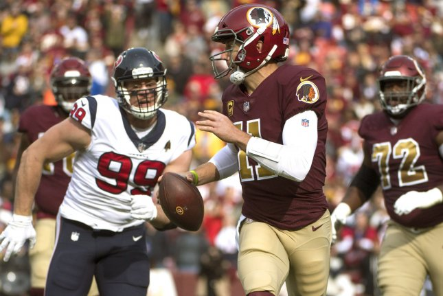 Washington Redskins quarterback Alex Smith (11) scrambles from Houston Texans defensive end J.J. Watt (99) during their game at FedEx Field in Landover, Maryland on November 18, 2018. Photo by Kevin Dietsch/UPI