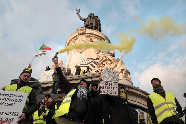Yellow Vest demonstrators hold placards and light flares beneath the statue of Marianne, a symbol of the French Republic, in Paris, early February. Photo by Eco Clement/UPI