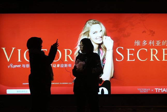 Chinese women take photos in front of a Victoria's Secret advertisement Tuesday in Beijing, China. The World Bank report said accumulated debt in China is making a major impact on anticipated global growth in 2020. Photo by Stephen Shaver/UPI