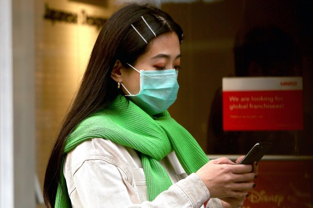 A woman wears a mandatory face mask at an empty international shopping mall in Beijing on Tuesday. Chinese officials said Thursday, the coronavirus epidemic has peaked there. Photo by Stephen Shaver/UPI