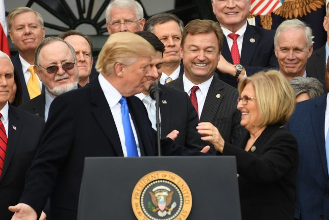 President Donald Trump greets Rep. Diane Black, R-Tenn., after discussing the passage of the Republican tax bill on December 20. Black on Wednesday announced she will resign her post on the House Budget Committee. Photo by Pat Benic/UPI