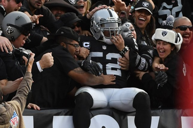 Oakland Raiders defensive end Khalil Mack (52) leaps into the stands after intercepting a pass by Carolina Panthers quarterback Cam Newton in the second quarter on November 27, 2016 at the Oakland Alameda County Coliseum in Oakland, California. File photo by Terry Schmitt/UPI