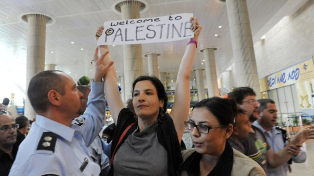 An Israeli undercover policewoman (R) arrests a left-wing activist holding a pro-Palestinian slogan at Ben Gurion Airport near Tel Aviv on April 15, 2012. Hundreds of Israeli police, many undercover, were deployed at the airport to block the arrival of pro-Palestinian activists taking part in a 'Welcome to Palestine' fly-in. Israel vowed to prevent entry of activists, warning foreign airlines they would be forced to foot the bill for the activists' immediate return home. UPI/Debbie Hill