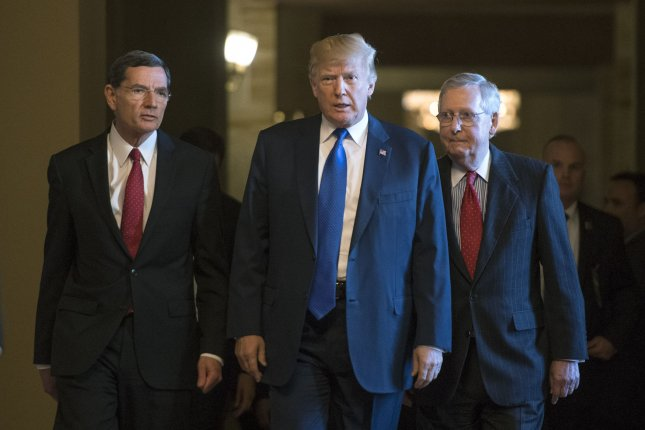 President Donald Trump (C) walks with Senate Republican leader Mitch McConnell (R), R-Ky., and Chairman of the Senate Republican Policy Committee John Barrasso, R-Wyo., as they make their way to a meeting with the Senate Republican caucus on Tuesday at the U.S. Capitol Building. Photo by Kevin Dietsch/UPI