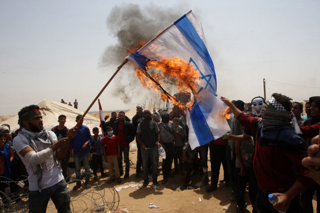 Palestinians burn an Israeli flag during a protest in Khan Younis in the southern Gaza Strip. File Photo by Ismael Mohamad/UPI
