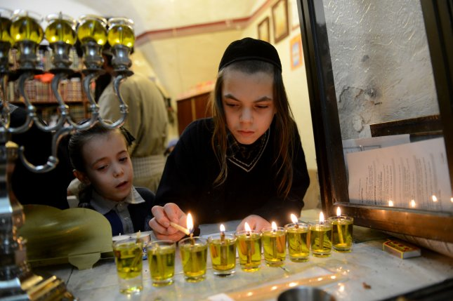 An Ultra-Orthodox Jewish boy lights candles on the eighth and final night of the Jewish holiday of Hanukkah in Mea Shearim in Jerusalem, December 23, 2014. Hanukkah commemorates the rededication of the Holy Temple in Jerusalem at the time of the Maccabean Revolt against the Seleucid Empire in 165 B.C. UPI/Debbie Hill
