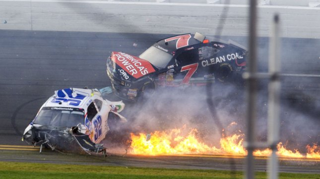 Kyle Larson's #32 car, missing its engine and on fire, slides over the finish line ahead of Regan Smith's #7 car after a wreck on final turn of the NASCAR Nationwide Series DRIVE4COPD 300 auto race at Daytona International Speedway in Daytona Beach, Fla., Feb. 23, 2013. UPI/Mark Wallheiser
