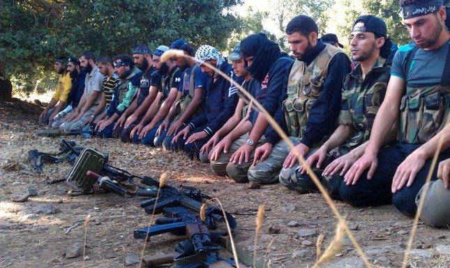 Members of the Free Syrian Army perform prayers in Damascus in August 13, 2012 after government forces shelled a number of areas in northern Syria part of efforts by the regime to target rebel strongholds. UPI