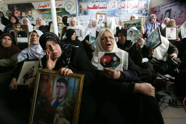 Palestinians hold portraits of jailed relatives during a protest at the Red Cross offices in Gaza City to demand the release of some 11,000 Palestinian prisoners held in Israeli jails on March 23, 2009. The Islamist Hamas movement had demanded Israel free hundreds of Palestinian prisoners in return for captured Israeli soldier Gilad Shalit, but Israel's outgoing Prime Minister Ehud Olmert has blamed Hamas for the failure of Egyptian-mediated talks aimed at securing a prisoner exchange. (UPI Photo/Ismael Mohamad)