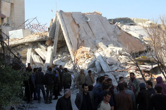 People stand around the rubble of a hospital supported by Doctors Without Borders (MSF) near Maaret al-Numan, in Syria's northern province of Idlib, on February 15, 2016. Photo by Omar Haj Kadour/ UPI