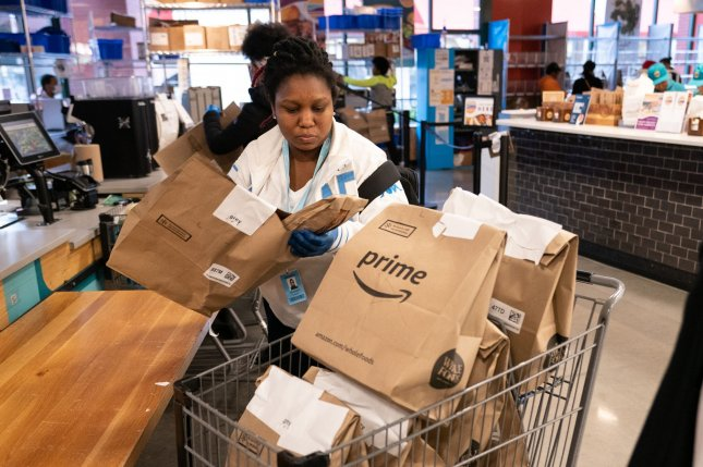 An independent contractor places Amazon Prime groceries into a cart as she organizes customer deliveries Tuesday inside a Whole Foods Market in Silver Spring, Md. Photo by Kevin Dietsch/UPI