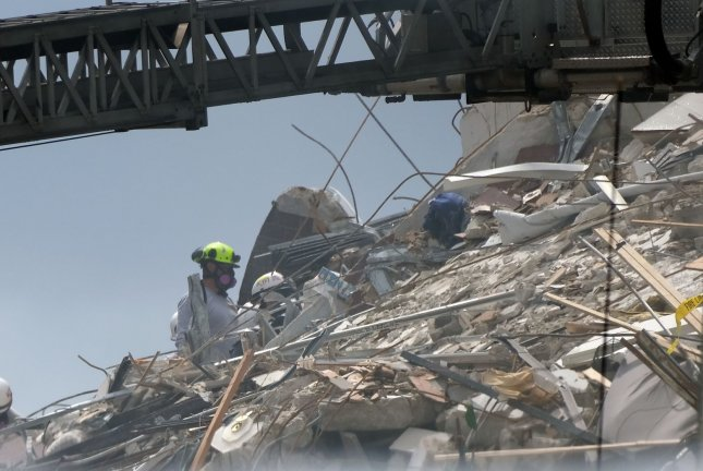 Rescue workers and heavy earth-moving equipment are seen working on the mound of the partially collapsed building in Surfside, Fla., on Friday. Photo By Gary I Rothstein/UPI