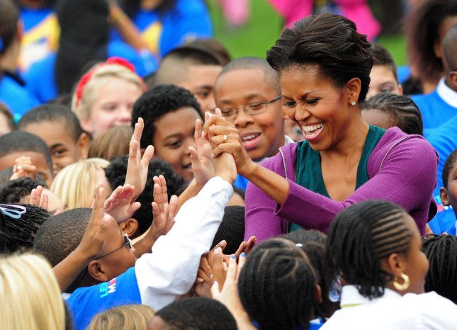 First Lady Michelle Obama greets local area school children after they attempted to break the Guinness World Record title for the most people doing jumping jacks in a 24-hour period, at the White House in Washington on October 11, 2011. UPI/Kevin Dietsch