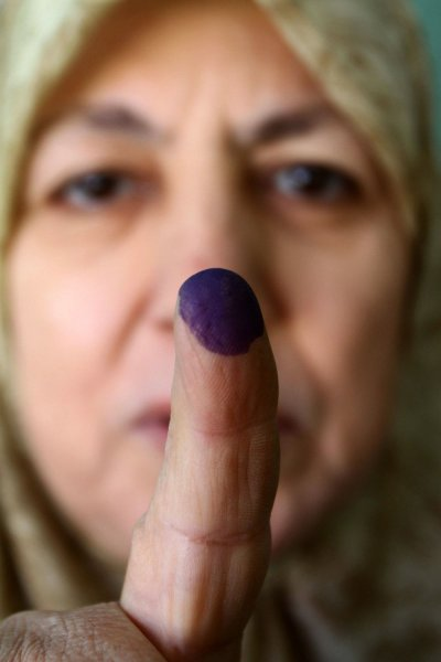 An Egyptian woman shows her ink-stained finger during the run-off of the first round of parliamentary voting in the Cairo neighbourhood of al-Manial on December 5, 2011. IUPI/Ashraf Mohamad