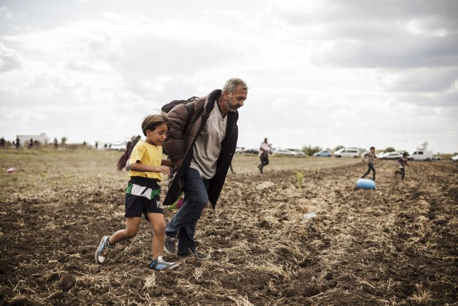 This Syrian father and son running were tripped Tuesday near Roszke by a Hungarian camerawoman whose actions generated worldwide condemnation. Syrian and other refugees were sleeping for days in the fields waiting their chance to get a bus that will take them to a registration center nearby. Photo by Achilleas Zavallis/UPI