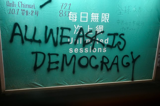 Grafitti on a billboard calls for democracy in Hong Kong. Sunday's District Council elections are one of the few chances for Hong Kongers to exercise their voting rights. Photo by Thomas Maresca/UPI
