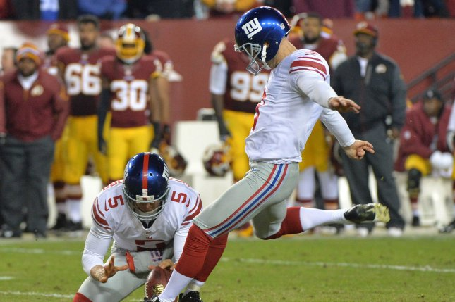 New York Giants kicker Josh Brown kicks a 39-yard field goal as Steve Weatherford holds the ball in the fourth quarter against the Washington Redskins at FedEx Field in Landover, Maryland, December 1, 2013. The Giants defeated the Redskins 24-17. UPI/Kevin Dietsch