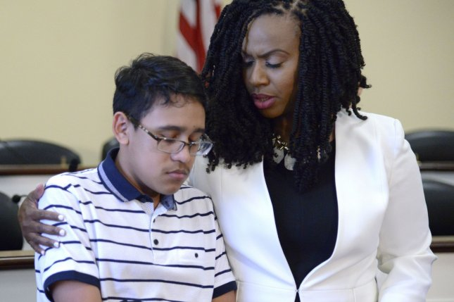 Sixteen-year-old Jonathon Sanchez, of Honduras, is embraced by Massachusetts Rep. Ayanna Pressley Wednesday during a news conference at the U.S. Capitol. Photo by Mike Theiler/UPI