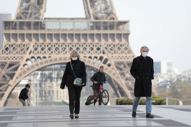 Residents wear masks to protect themselves from the coronavirus as they visit the Eiffel Tower in Paris, France on March 26. File Photo by Eco Clement/UPI