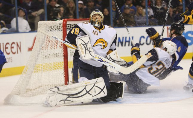 Buffalo Sabres goaltender Patrick Lalime watches the puck as Sabres Patrick Kaleta and St. Louis Blues Jay McClement crash into the net during the first period at the Scottrade Center in St. Louis, Dec. 27, 2009. UPI/Bill Greenblatt