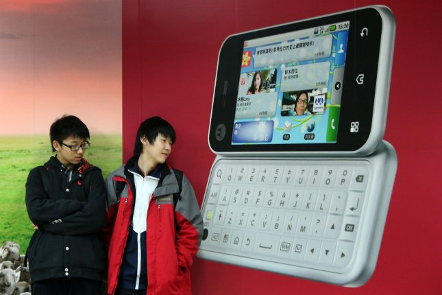 Chinese teenagers stand in front of a Motorola mobile phone advertisement in Beijing. Chinese phone users have one of the highest mobile phone turnover rates in the world. On average, a Chinese phone user discards an old phone every 8-12 months, but none of the phones are being recycled, according to a Chinese media report. Photo by Stephen Shaver/UPI